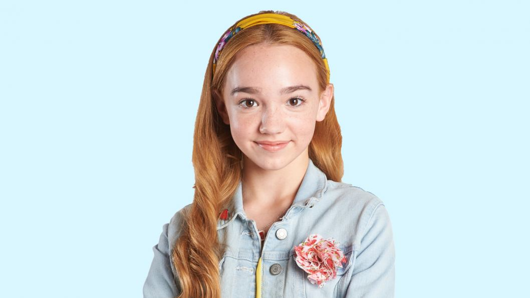 A portrait of a teenage girl with red hair. She is wearing a yellow headband and a light blue jean jacket.