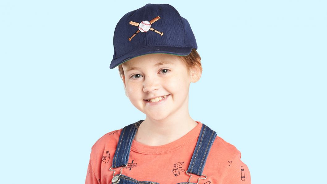 A portrait of a young girl, wearing a navy blue baseball hat, overalls and a light orange top.