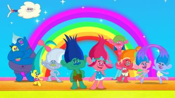 Colourful trolls, with big hair, standing in front of a blue sky and a rainbow.