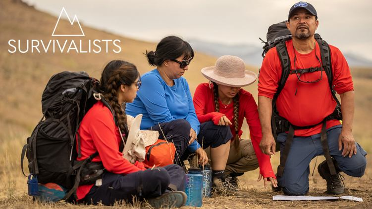 Two parents and their two teenage daughters, wearing large trekking backpacks,  sitting on the ground and looking at a map in the middle of a yellow field.