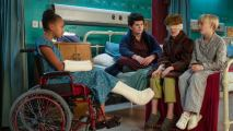 Three kids with injuries sitting on a hospital bed and a young girl sitting in a wheelchair with a cast on her arm and leg.