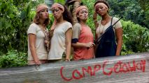 Four young women with serious looks on their faces standing in a jungle in front of a wooden log. They are wearing bandanas and have markings on their faces.