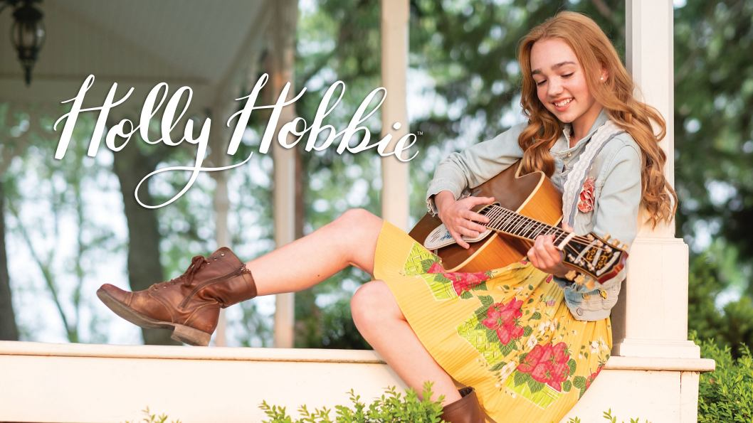 A teenage girl sitting on the porch playing her guitar and smiling. She had red hair and is wearing a yellow dress, jean jacket and brown combat boots.